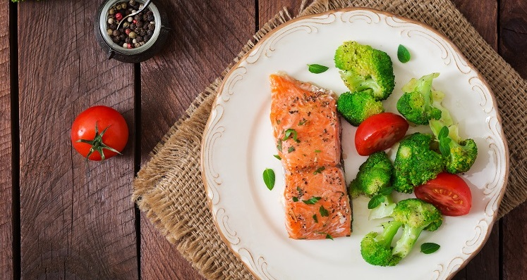 Baked fish salmon garnished with broccoli and tomato. Dietary menu. Fish menu. Seafood - salmon. Top view