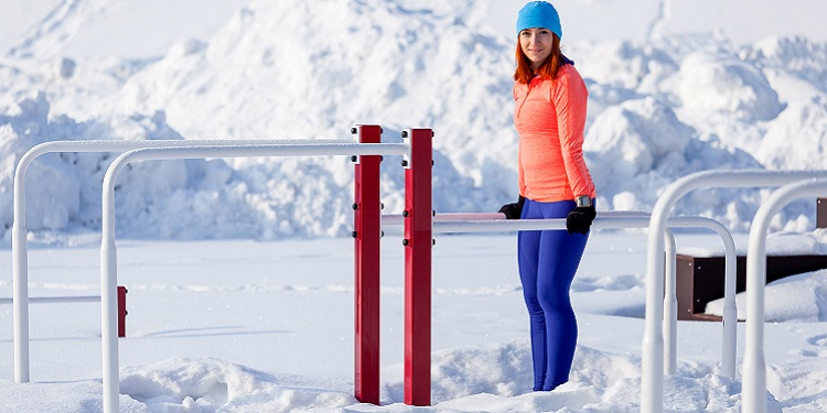 A young woman in bright sportswear makes pull-ups on horizontal bars on a bright winter day