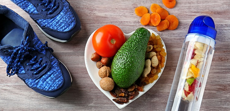 Healthy food, sneakers and water bottle on wooden background
