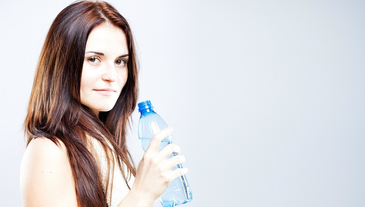 Beautiful young woman after fitness exercise proposing bottle of water