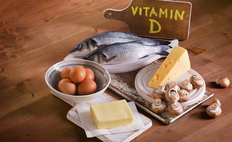 Foods containing vitamin D on a wooden background.